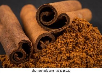 Cinnamon sticks with cinnamon powder on stone plate background