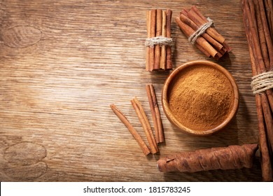 Cinnamon sticks and powder on a wooden table, top view