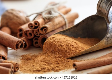 Cinnamon sticks and powder on a wooden table. Closeup view with details. Christmas holiday preparation