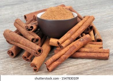 Cinnamon sticks and cinnamon powder ramekin in close-up