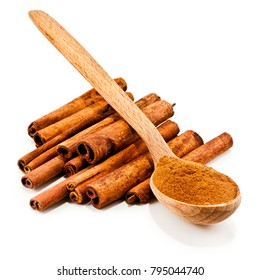 Cinnamon sticks and powder of cinnamon in a wooden spoon isolated on white background.
