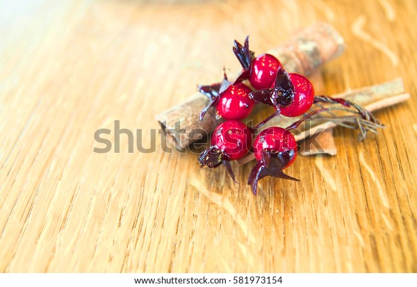 cinnamon sticks with red berries on a wooden background