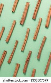 Cinnamon sticks sorted into pattern - overhead shot on a muted green background