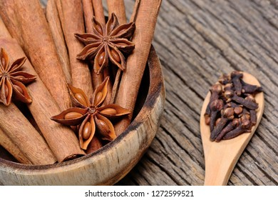Cinnamon sticks with star anise in a bowl and cloves in a wooden spoon on table