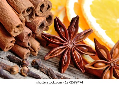 Cinnamon sticks with star anise, cloves and sliced of orange fruit on old wood table