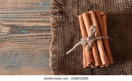 Cinnamon sticks wrapped with rope on wooden rustic table