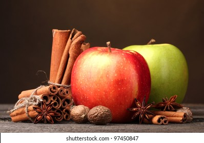 Cinnamon sticks,apples nutmeg and anise on wooden table on brown background