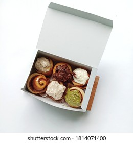 Cinnamonrolls with various frosting in the white box