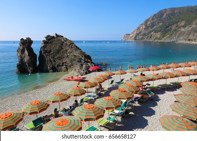 Cinque Terre, Italy - August 28, 2016: Colorful beach umbrellas snake across the beach at Monterosso al Mare on Italy's Cinque Terre coast.