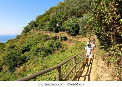 Cinque Terre, Italy - August 28, 2016: Hikers walk along a trail between Monterosso al Mare and Vernazza in Italy's Cinque Terre national park.