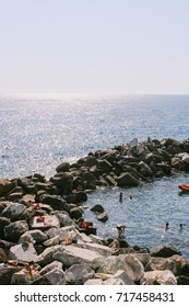 CINQUE TERRE, ITALY - CIRCA JULY 2017: People bathing and sunbathing in rocky waters near the harbor of one of the villages in Cinque Terre, northern Italy.