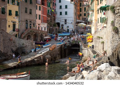 CINQUE TERRE, ITALY - JULY 20, 2012: Hot summer season and sunbathing tourists in Riomaggiore town, Cinque Terre, Italy