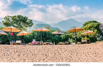 CIRALI, TURKEY – OCTOBER 03, 2018: Beach umbrellas on Turkish Riviera in Cirali, Antalya Province, Turkey, Asia