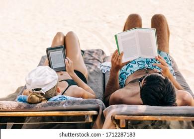 CIRALI, TURKEY – OCTOBER 8, 2018: Couple reading ebook and book on beach in Cirali, Turkey.