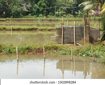 Cirata, West Java / Indonesia - 3-1-2015: Traditional public toilet at a village by the natural fishing pool. It has no roof, the walls just made of zinc plate, and the floor made of bamboo wood.