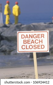 "CIRCA 1990 - A sign warning, ""Danger Beach Closed"" with cleanup crews in the background"