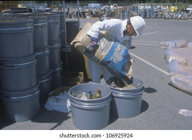 CIRCA 1990 - A worker pouring the contents of a bag into a container of waste materials at waste cleanup site on Earth Day at the Unocal plant in Wilmington, Los Angeles, CA