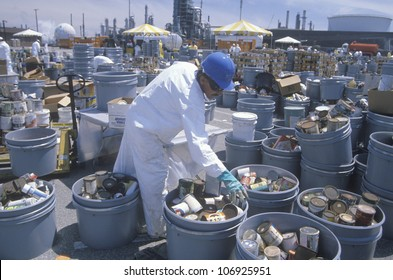 CIRCA 1990 - Worker sorting toxic wastes at waste cleanup site on Earth Day at the Unocal plant in Wilmington, Los Angeles, CA