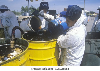 CIRCA 1990 - Workers handling toxic household wastes at waste cleanup site on Earth Day at the Unocal plant in Wilmington, Los Angeles, CA
