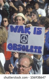 "CIRCA 1991 - Sign ""War is obsolete"" at peace rally,  Los Angeles, California"