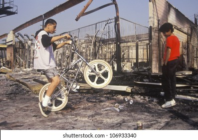 CIRCA 1992 - Inner city youth riding bicycle at burned out building, South Central Los Angeles, California