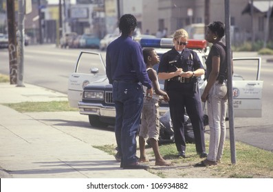 CIRCA 1992 - Policewoman taking a report, South Central Los Angeles, California