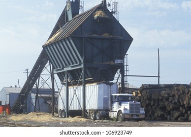 CIRCA 1992 - Sawdust and wood chips are loaded into a large truck at a paper mill