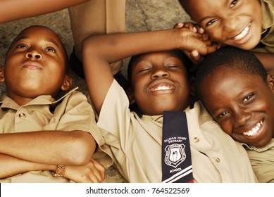 CIRCA 2010 Jamaica, Kingston, close-up portrait of an African schoolboy lying down with eyes closed surrounded with friends