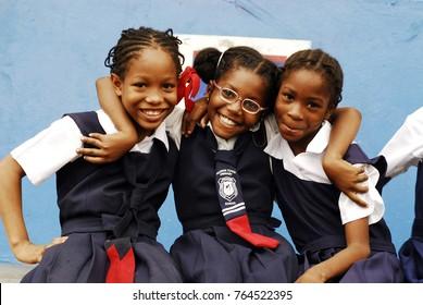 CIRCA 2010 Jamaica, Kingston, portrait of three African schoolgirls smiling with arm around
