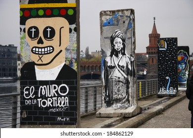 """CIRCA APRIL 2013 - BERLIN: remnants of the former Berlin Wall (""""Berliner Mauer"""") with graffities and paintings on the mediaspree in the Friedrichshain district of Berlin."""