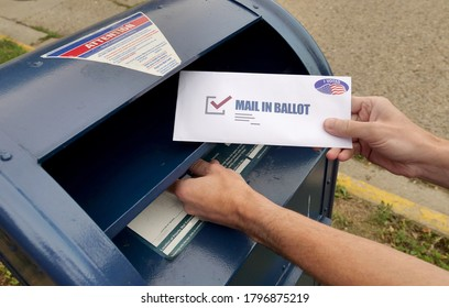 Circa August, 2020 - A man puts an absentee mail-in ballot in the mailbox.