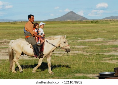 Circa Harhorin, Mongolia - August 19, 2006: Unidentified Mongolian man rides on horseback with two kids circa Harhorin, Mongolia. Mongolians teach kids riding on horseback from a very young age.