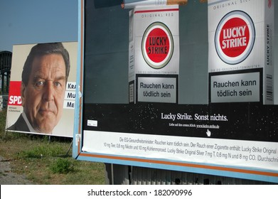 CIRCA SEPTEMBER 2005 - BERLIN: Gerhard Schroeder (SPD) next to an ad for Luky Strike cigaretteson an election poster to the upcoming general elections in Germany 2005.