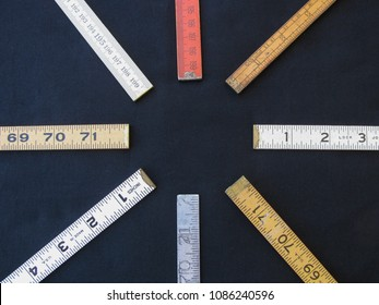 A circle arrangement of folding rulers on black limbo suggests concepts of measurement, precision, accuracy, with center copy space.