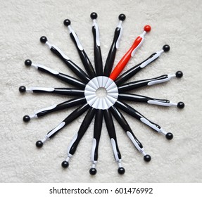 circle of black ballpoint pens with a red one