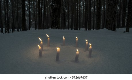 Circle of candles in dark winter forest