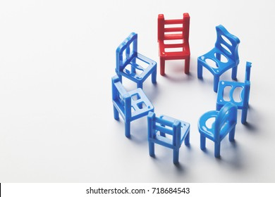 Circle of chairs with one odd one out.