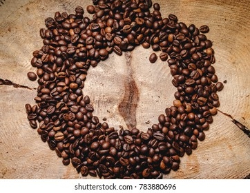 Circle of coffee beans on a wooden background