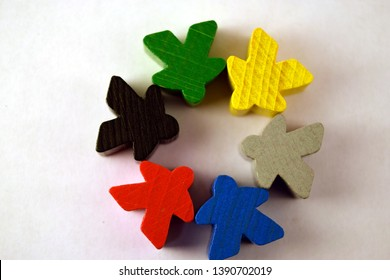 Circle of colorful meeples on white background