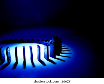 A circle of dominoes in a blue light