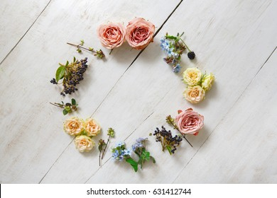 Circle of fresh and dried flowers and berries on white wood background, top view, copy space