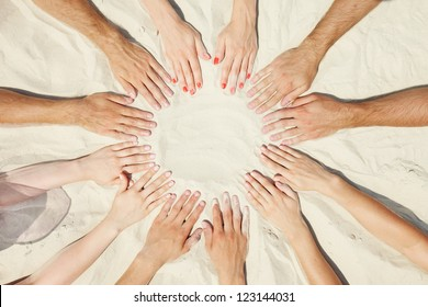 Circle of hands of friends on sand
