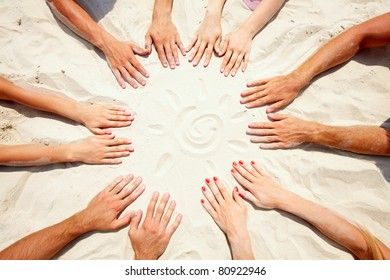 Circle of hands on sand with a sun