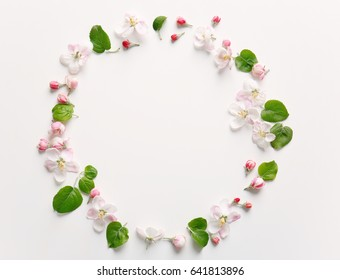 Circle made with blooming flowers on white background