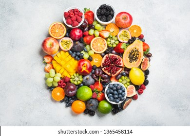 Circle made of healthy raw rainbow fruits, mango papaya strawberries oranges passion fruits berries on oval serving plate on light concrete background, top view, copy space, selective focus