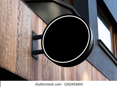 circle mockup of street store template signboard on empty wood wall