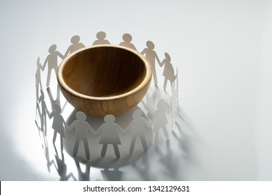 Circle of paper people holding hands in front of big empty bowl. Famine, overpopulation concept.