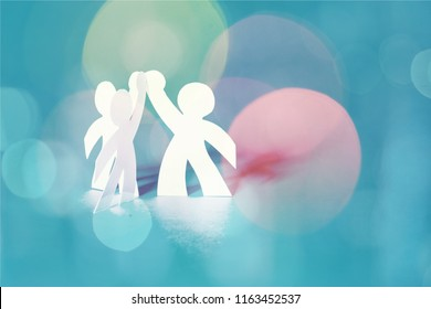Circle of paper people on abstract background
