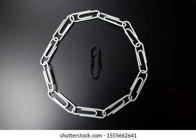 A circle of paperclips with one in the middle that is not fitting in and is surrounded. Symbolic representation of not fitting in the group and being bullied. Feeling excluded.