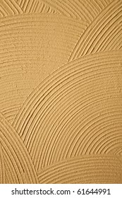 Circle patterns and texture in a yellow-gold stucco wall